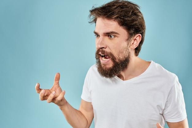 Homem com expressão facial descontente, gesticulando com azul de estilo de vida de estúdio de mãos.