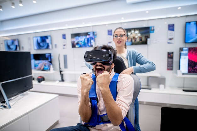 Homem com expressão facial espantada, experimentando a tecnologia vr. mulher em pé nas costas. interior da loja de tecnologia.