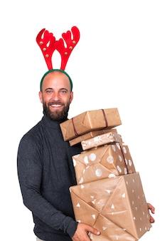 Homem com fantasia de rena olhando para a câmera carregando presentes de natal fundo branco vertical
