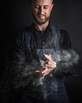 Homem com farinha de pão nas mãos