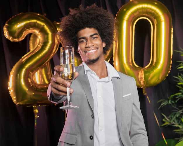 Homem com feliz ano novo 2020 balões e taça de champanhe