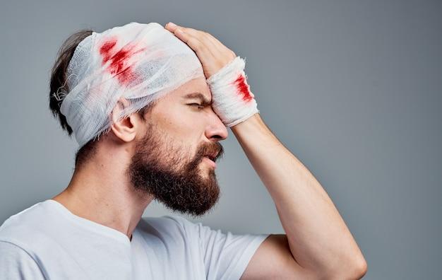 Homem com ferimento no braço e na cabeça com enfaixamento hospitalar