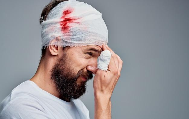 Homem com ferimento no braço e na cabeça com enfaixamento, problema hospitalar com lesão