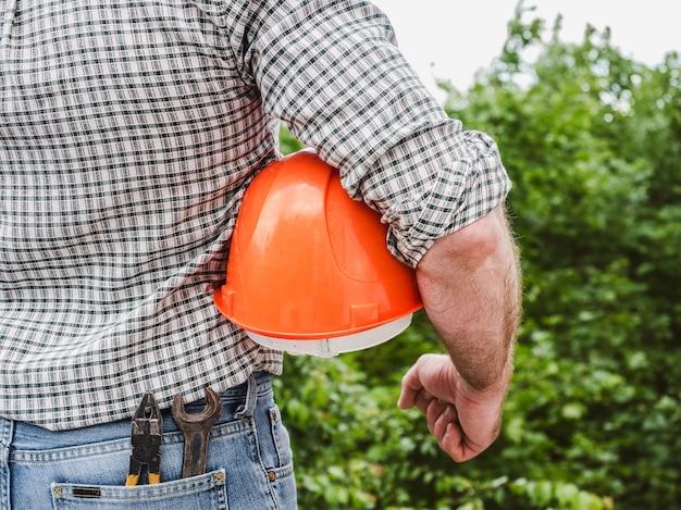 Homem com ferramentas, segurando um capacete de segurança