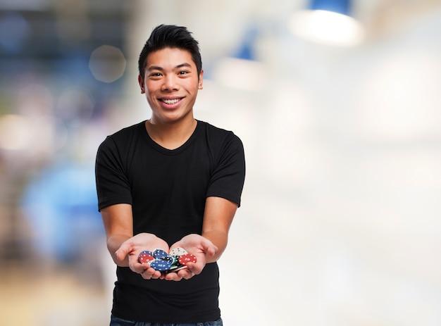 Homem com fichas de casino em suas mãos