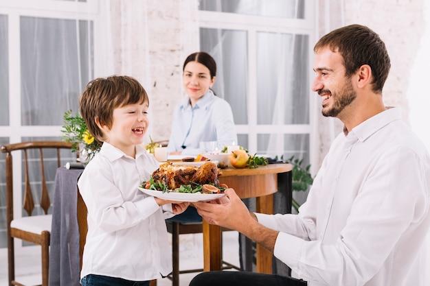 Homem, com, filho, segurando, galinha, ligado, prato