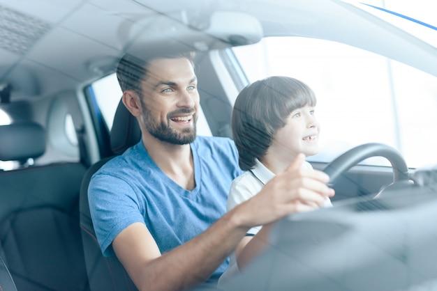 Homem com filho sorri e dirige um carro.