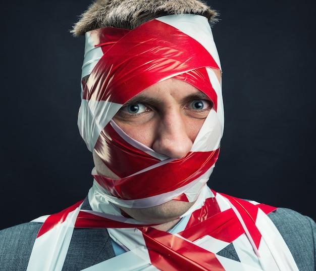 Homem com fita adesiva despojada sobre o corpo
