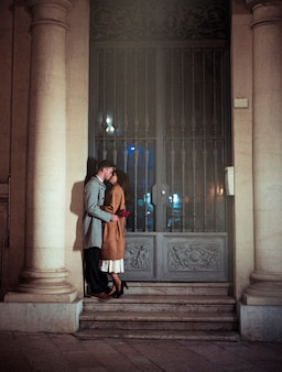 Homem, com, flores vermelhas, beijando, mulher, ligado, lábios