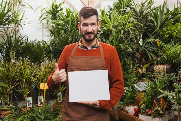 Homem com folha de papel gesticulando polegar para cima