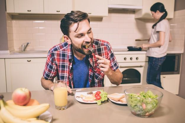 Homem com fome está sentado à mesa e morder a refeição que ele tem no garfo. o cara está mantendo os olhos fechados. garota fica no fogão e cozinha comida.