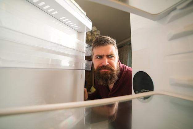 Homem com fome, procurando comida na geladeira vazia. homem barbudo olhando para a geladeira vazia. homem intrigado na cozinha.