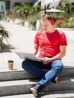 Homem com fones de ouvido ao ar livre com café e laptop