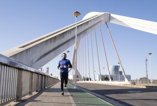 Homem com fones de ouvido azuis usando seu celular enquanto corre na rua