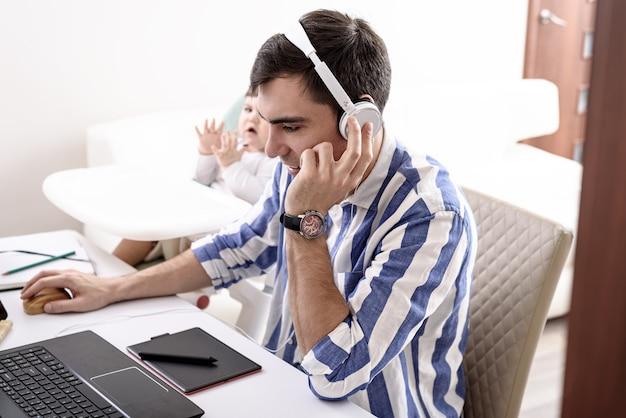 Homem com fones de ouvido brancos sentado trabalhando no laptop com criança, trabalho remoto em casa com crianças, conceito freelancer