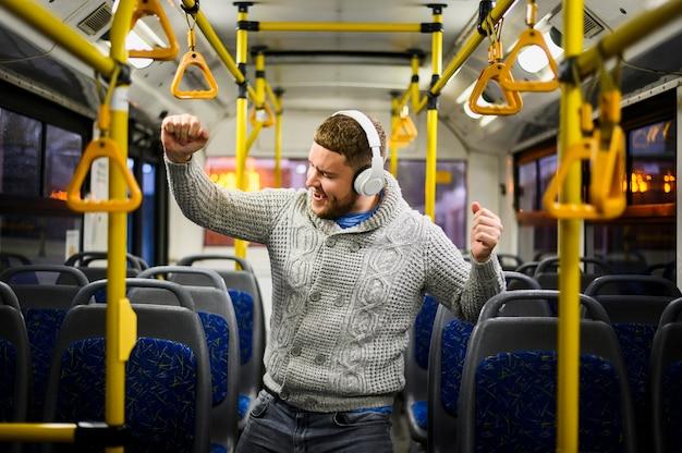 Homem com fones de ouvido dançando sozinho no ônibus