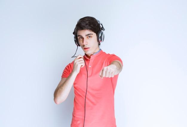 Homem com fones de ouvido, desejando o punho à frente.
