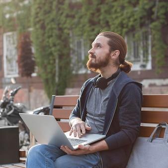 Homem com fones de ouvido e laptop na cidade
