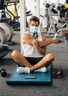 Homem com fones de ouvido e máscara médica na academia malhando no tapete