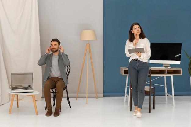Homem com fones de ouvido e mulher lendo