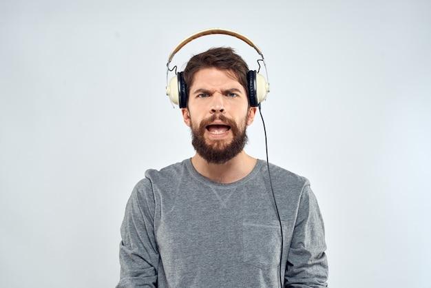 Homem com fones de ouvido ouve música estilo de vida moderno estilo tecnologia luz de fundo. foto de alta qualidade
