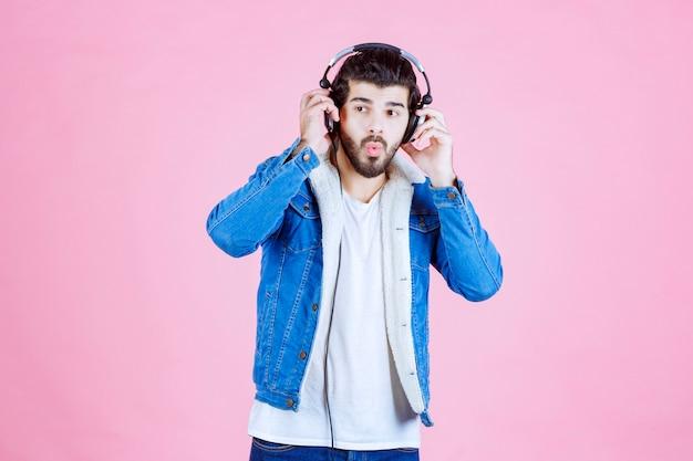 Homem com fones de ouvido parece confuso