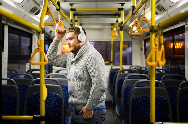 Homem com fones de ouvido, passando por transportes públicos