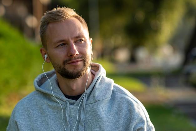 Homem com fones de ouvido relaxando ao ar livre
