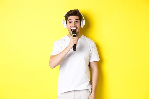 Homem com fones de ouvido segurando um microfone, cantando uma canção de karaokê, em pé sobre uma parede amarela com roupas brancas