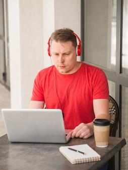 Homem com fones de ouvido, tomando café ao ar livre e trabalhando no laptop