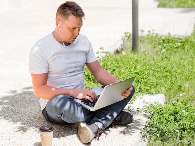 Homem com fones de ouvido trabalhando no laptop ao ar livre