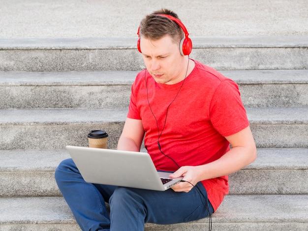 Homem com fones de ouvido trabalhando nos degraus com laptop