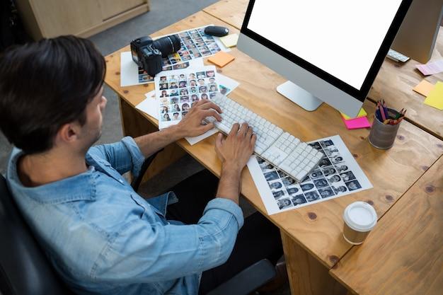 Homem com fotografias trabalhando no desktop pc