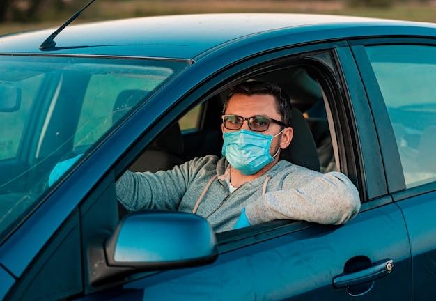 Homem com frasco de desinfetante antibacteriano se protege de bactérias no próprio carro