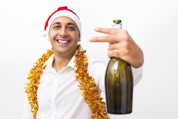 Homem com garrafa de champanhe mostrando dois dedos