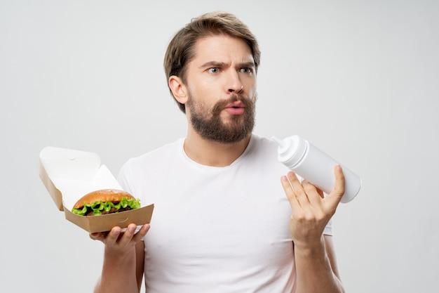 Homem com goldberg nas mãos camiseta branca com dieta de fast food