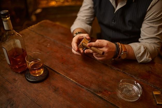 Homem com guilhotina corta um charuto, mesa de madeira no fundo