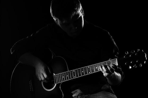 Homem com guitarra na escuridão