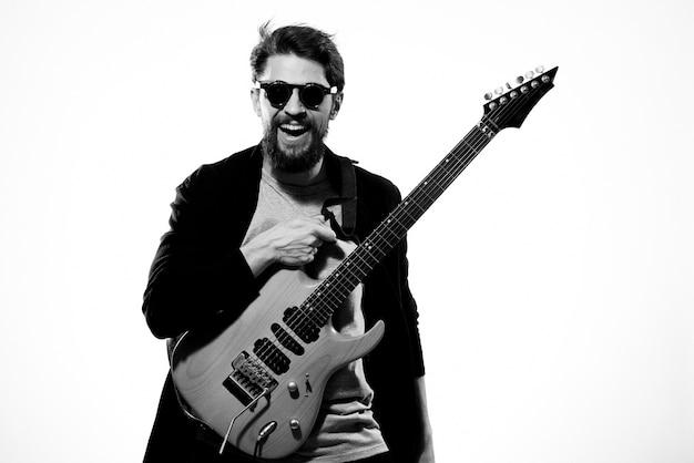 Homem com guitarra nas mãos músico rock star performance estilo de vida e luz de fundo