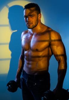 Homem com haltere. cara de fisiculturista muscular fazendo exercícios.