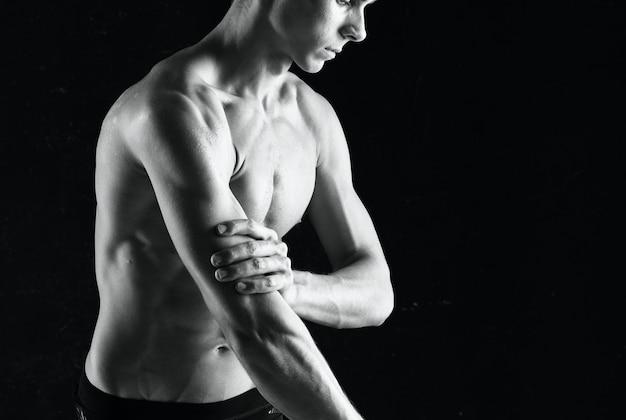 Homem com halteres nas mãos e exercícios de musculação