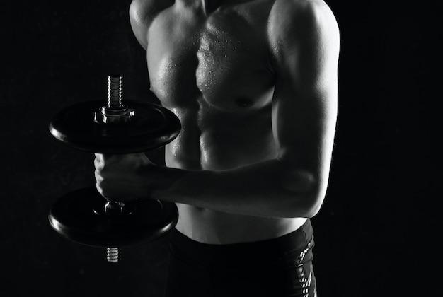 Homem com halteres nas mãos fundo escuro de treino de corpo musculoso nu