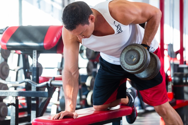 Homem com halteres no esporte no ginásio de fitness