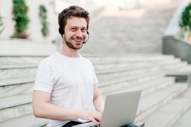 Homem, com, headset, e, laptop, ao ar livre