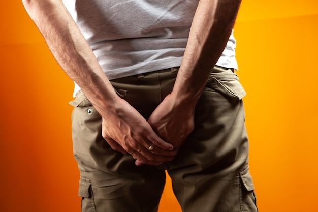Homem com hemorróidas segurando a bunda em fundo laranja