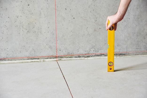 Homem com instrumento de nível de piso, verificar piso e paredes