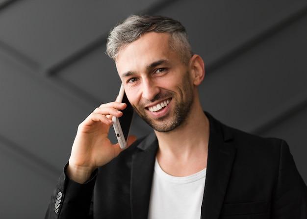 Homem com jaqueta preta fala ao telefone e sorri