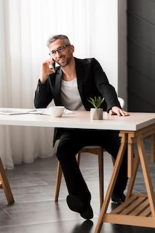 Homem com jaqueta preta, falando ao telefone a visão longa