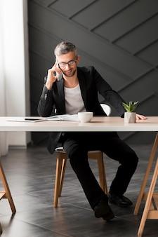 Homem com jaqueta preta falando ao telefone dentro de casa