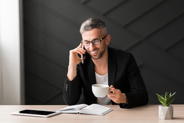 Homem com jaqueta preta falando ao telefone e tomando café